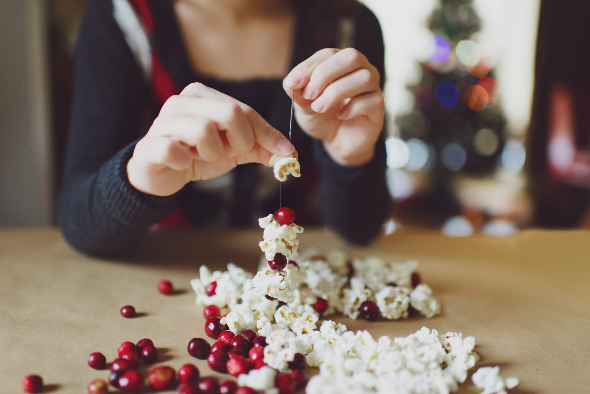Making Christmas garland of fresh cranberries and popcorn.